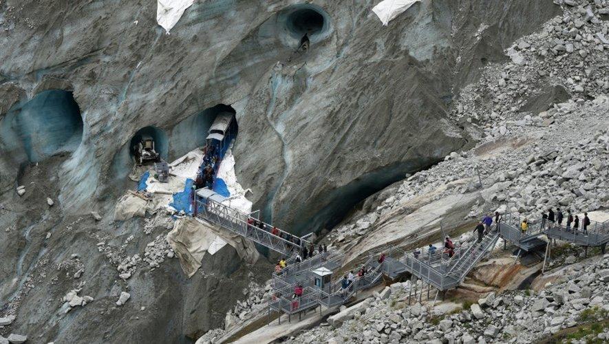 """Des visiteurs marchent dans l'escalier, à flanc de falaise, qui permet de rejoindre la """"Mer de glace"""", à Chamonix-Mont-Blanc, dans les Alpes françaises, le 8 juin 2015"""