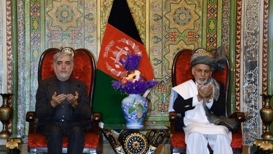 Le président afghan Ashraf Ghani (d) et le numéro deux du régime Abdullah Abdullah prie durant une visite à Jalalabad, dans la province de Nangarhar, le 23 avril 2015