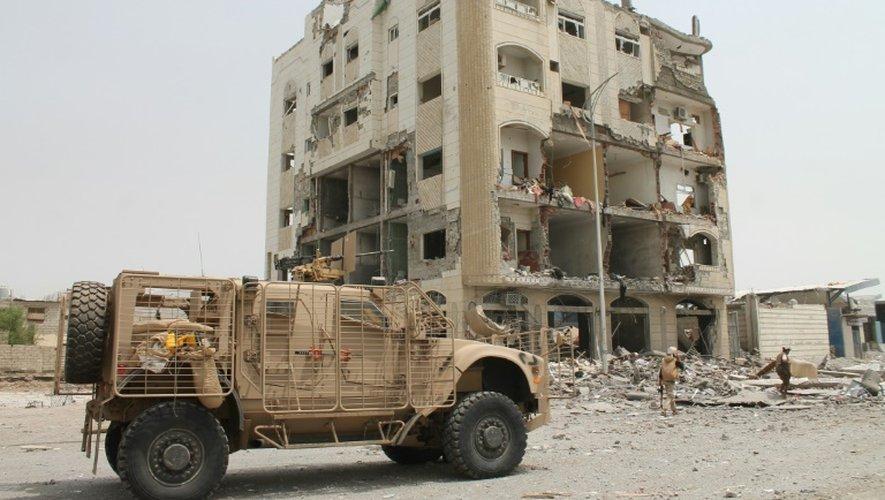 Des combattants yéménites fidèles au président en exil Abed Rabbo Mansour Hadi devant un bâtiment endommagé à Aden, le 15 juillet 2015