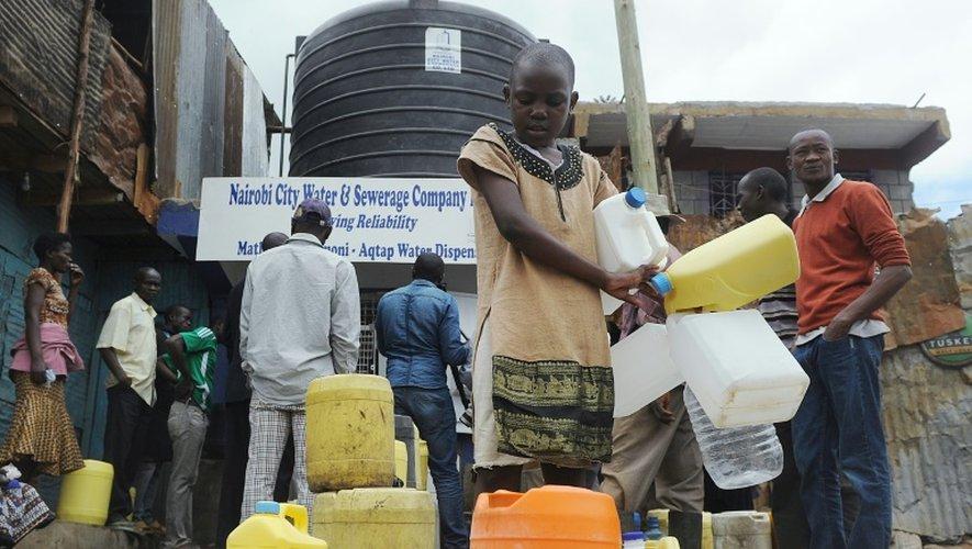 Des kényans viennent chercher de l'eau dans un distributeur automatique, dans un bidonville de Nairobi le 24 juin 2015