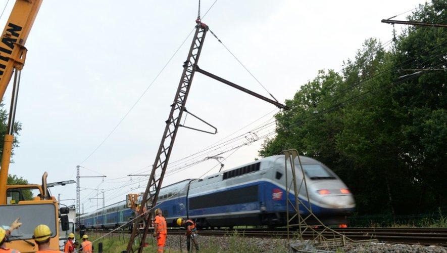 Des techniciens de la SNCF déplacent un pylône tombé sur les voies ferrées après un accident de voiture à Chalais près de Courlac dans le sud-ouest de la France, bloquant le trafic TGV le 17 juillet 2015