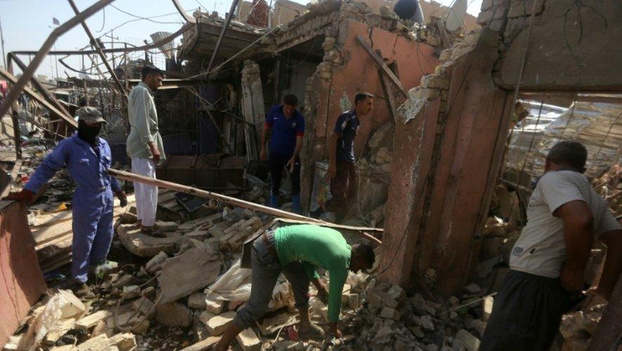 Des Irakiens fouillent le 18 juillet 2015 les décombres d'un bâtiment au lendemain d'une attaque à la voiture piégée la veille à Khan Bani Saad au nord de Bagdad