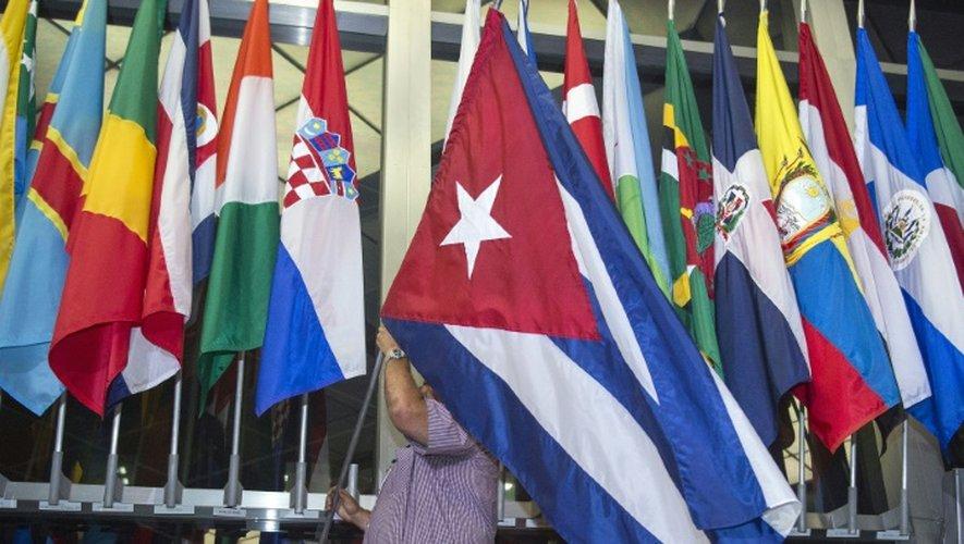Un homme ajoute le drapeau cubain au département d'Etat américain, le 20 juillet 2015