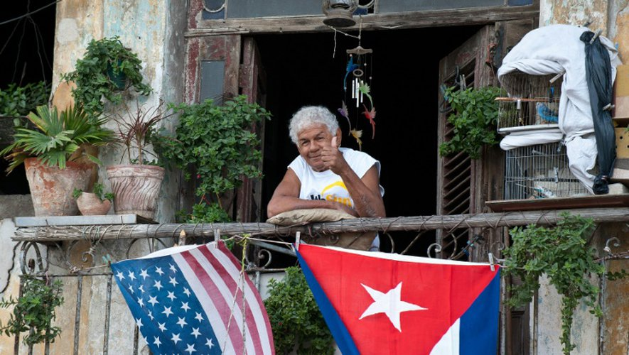 Un habitant de La Havane salue depuis son balcon décoré avec les drapeaux américains et cubains, pour célébrer en janvier 2015 l'annonce du rapprochement entre les deux pays