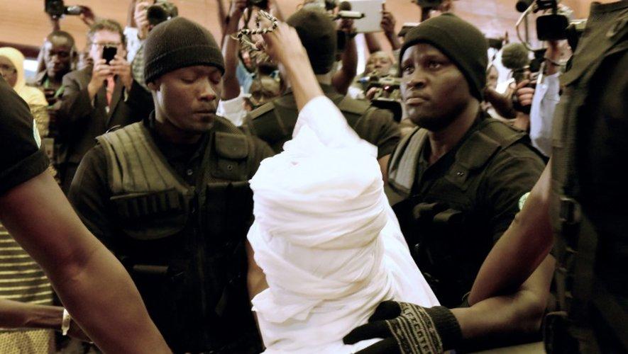L'ancien président tchadien Hissène Habré (c) est escorté par ses gardiens de prison dans la  salle du tribunal à Dakar pour son procès le 20 juillet 2015