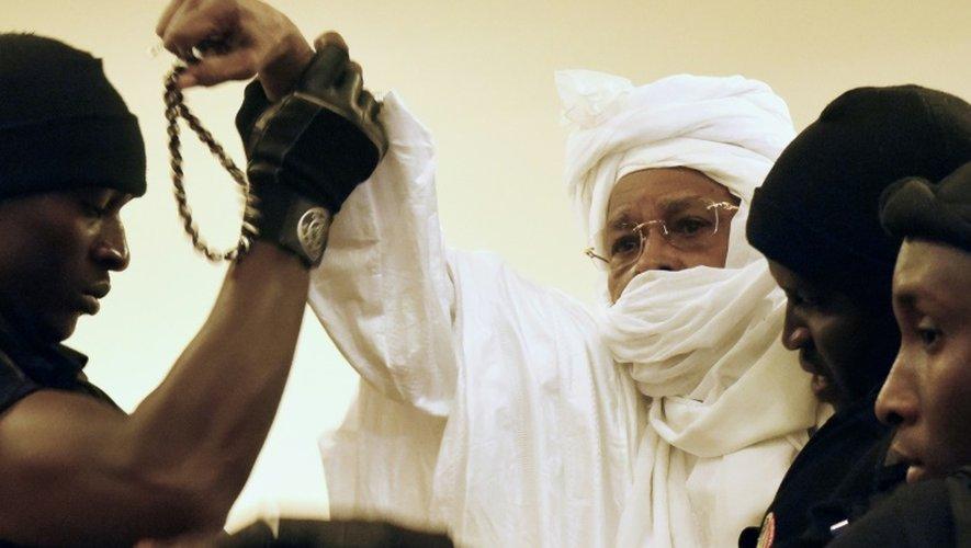 L'ex président tchadien Hissène Habré escorté par des gardiens de prison arrive au tribunal pour le premier jour de son procès à Dakar, le 20 juillet 2015