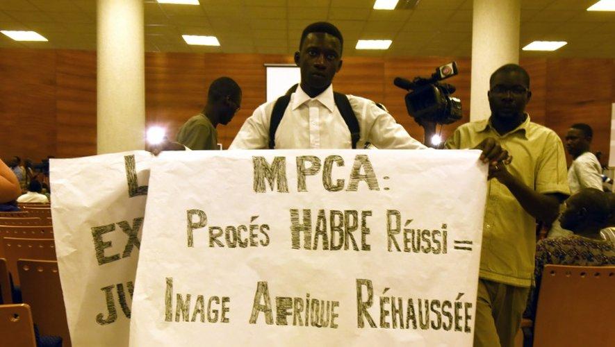 """Panneau proclamant """"procès Habré réussi = image Afrique rehaussée"""" tenu par un opposant dans la cour où se tient le procès de l'ancien dirigeant tchadien à Dakar le 20 juillet 2015"""