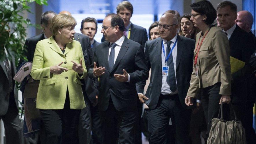 François Hollande discute avec la chancelière allemande Angela Merkel après une réunion bilatérale en marge d'un sommet de la zone euro, le 22 juin 2015 à Bruxelles