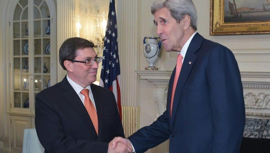 Le secrétaire d'Etat américain John Kerry (d) serre la main de son homologue cubain Bruno Rodriguez, le 20 juillet 2015 au département d'Etat à Washington