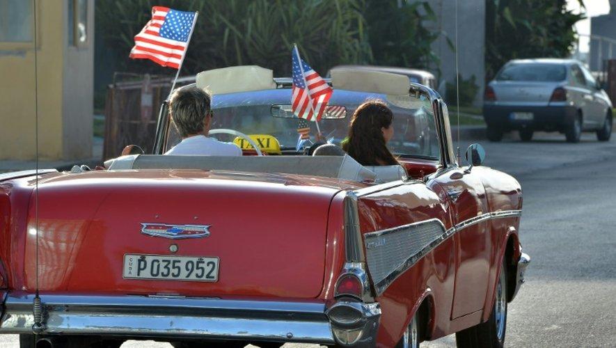 Une ancienne voiture ornée de drapeaux américains passe devant le bâtiment qui fera office d'ambassade américaine à La Havane, le 20 juillet 2015
