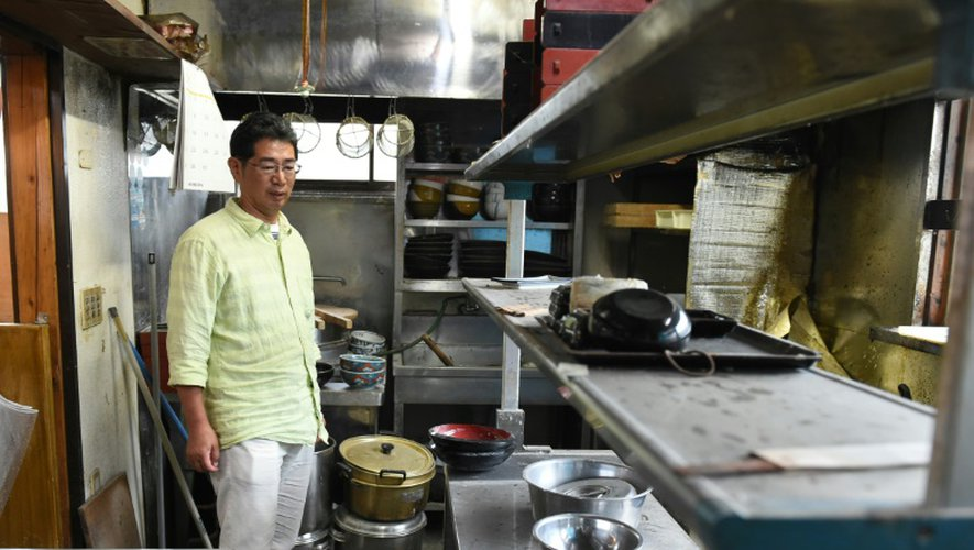 Satoru Yamauchi regarde le 16 juillet 2015 la cuisine couverte de poussière de son restaurant à Naraha, abandonnée dans l'urgence après l'accident dans la centrale de Fuhushima