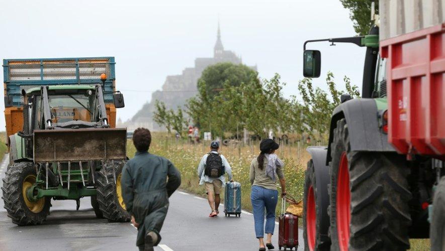 Des touristes passent les barrages des agriculteurs à pied pour se rendre le 21 juillet 2015 au Mont-Saint-Michel