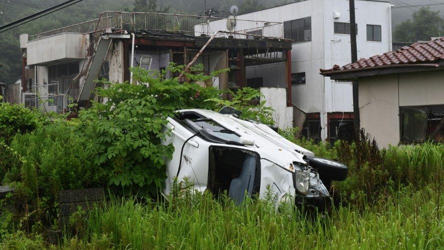 Photo prise le 16 juillet 2015 montrant un véhicule et des bâtiments endommagés par le tsunami de 2011 et restés en l'état quatre ans après dans le village de Tomioka au nord de Naraha dans la préfecture de Fukushima