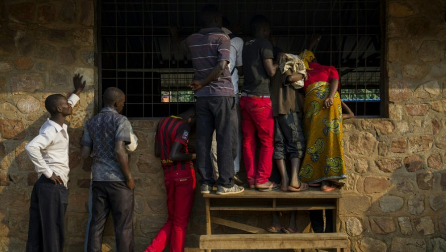 Des curieux regardent les opérations de dépouillement en cours dans un bureau de vote de Bujumbura, le 21 juillet 2015
