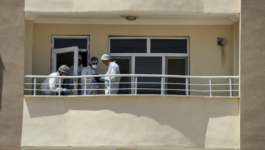 Des enquêteurs de la police scientifique travaillent sur le balcon d'un appartement où deux policers turcs ont été tués par balles à Ceylanpinar, à la frontière avec la Syrie, le 22 juillet 2015