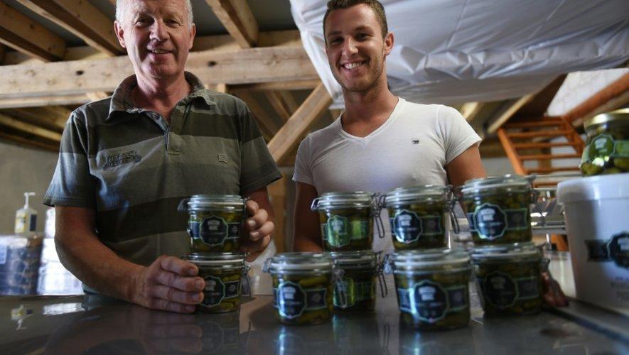 Florent Jeannequin (g) et son fils Henri, les derniers producteurs français de cornichons, qui fournissent l'Elysée, posent avec leurs bocaux le 15 juillet 2015 à Chemilly-sur-Yonne (centre)