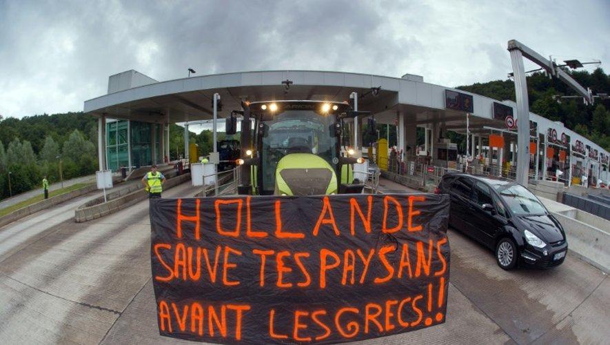 Drapeau interpellant le président François Hollande déployé sur un tracteur participant à un barrage des éleveurs sur l'autoroute A36 Sochaux-Besançon, à hauteur de L'Isle-sur-le-Doubs (Franche-Comté), le 23 juillet 2015