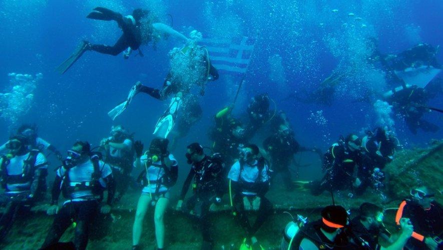 Un plongeur a récupéré un drapeau grec en explorant l'épave du Zenobia, le 25 juin 2015 au large de Chypre où ce bateau a sombré il y a 35 ans