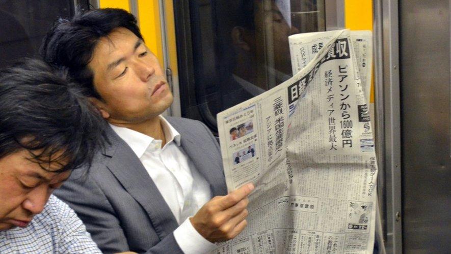 Un Japonais lit le journal financier Nikkei, à Tokyo, le 24 juillet 2015