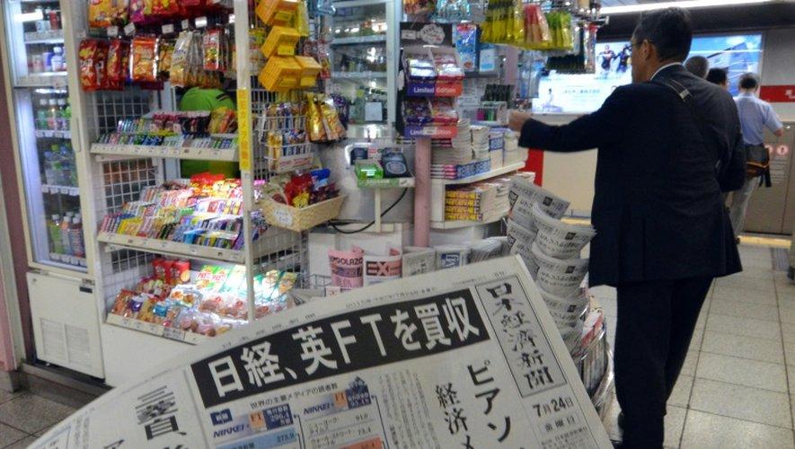 Un homme achète le journal financier Nikkei, à Tokyo, le 24 juillet 2015
