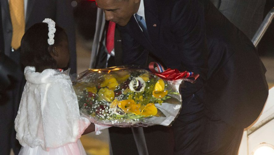 Une jeune fille kényane, Joan Wamaitha, 8 ans, remet un bouquet de fleurs de bienvenue au président Barack Obama le 24 juillet 2015 à sa descente de l'avion à l'aéroport international de Nairobi