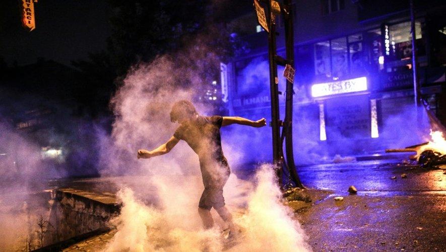 Un manifestant renvoie une grenade lacrymogène lors d'une manifestation le 24 juillet 2015 dans le quartier Gazi à Istanbul