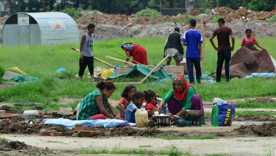 Une famille népalaise prépare le repas dans un camp de rescapés du séisme au Népal, le 23 juillet 2015 à Katmandou