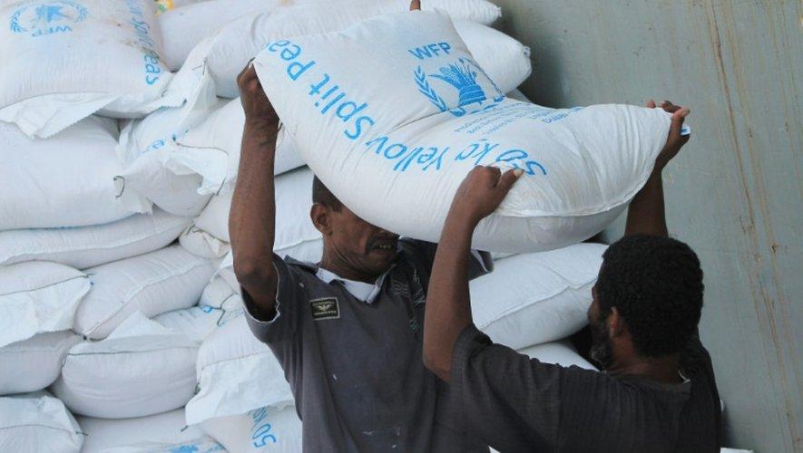 Des hommes déchargent l'aide humanitaire des bateaux à Aden pour la distribuer à la population le 21 juillet 2015