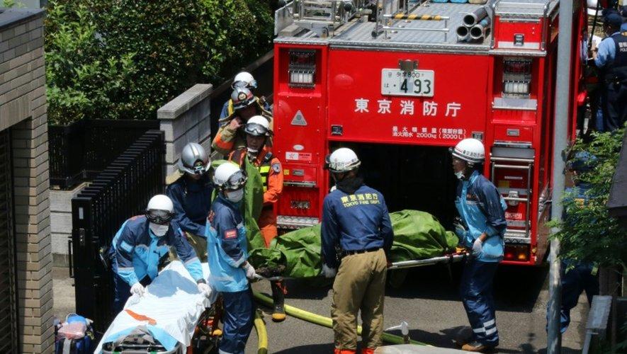 Evacuation d'une victime après le crash d'un avion de tourisme le 26 juillet 2015 sur une zone résidentielle de Tokyo