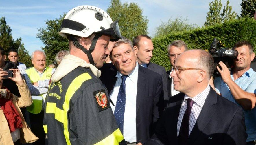 Le ministre de l'Intérieur Bernard Cazeneuve avec des pompiers le 26 juillet 2015 à Pessac