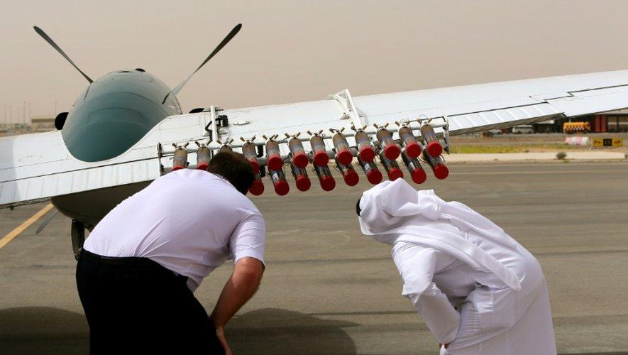 Un pilote et un fonctionnaire des Emirats arabes unis vérifient sur un avion Beechcraft les fusées destinées à injecter des cristaux de sels dans les nuages pour tenter de provoquer de la pluie, le 23 avril 2015 à l'aéroport d'Al-Aïn