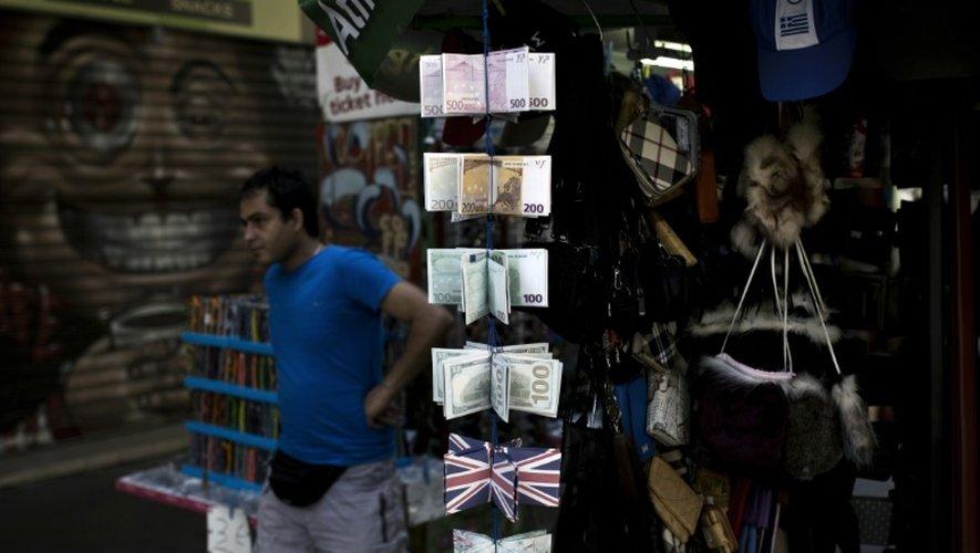 Un homme passe devant un présentoir avec des porte-monnaies remplis des imitations de billets d'euros, le 25 juillet 2015 à Athènes