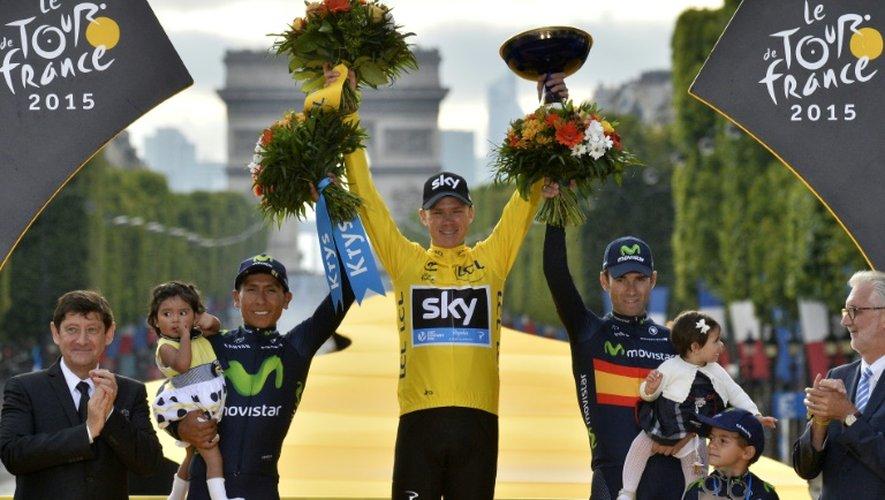 Le Britannique Chris Froome (c) célèbre sur le podium, entre Nairo Quintana et Alejandro Valverde, sa 2e victoire au Tour de France, le 27 juillet 2015 aux Champs-Elysées