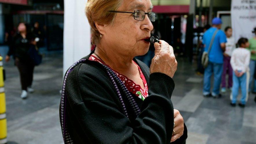 Une femme siffle devant le métro de Pantitlan à Mexico, lors d'une campagne contre de prévention du harcèlement sexuel, le 6 juillet 2016