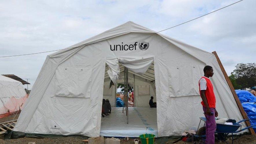 Un homme devant une tente Unicef dédiée aux patients infectés avec le virus Ebola à Monrovia le 12 août 2014