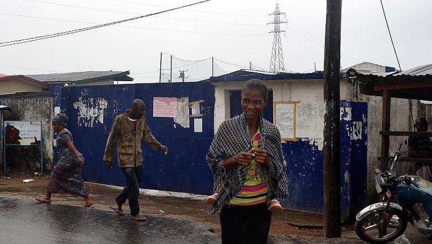 Des passants marchent devant une école transformée en centre d'isolement pour les malades d'Ebola d'où se sont enfuis 17 malades à la suite d'une attaque, le 17 août 2014 à Monrovia au Libéria