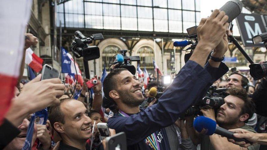 Mahiédine Mekhissi se photographie avec des fans, le 18 août 2014 à la gare de Lyon à Paris