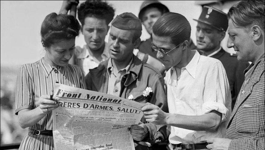 """Des français lisent le journal """"Front National de lutte pour l'indépendance de la France"""" durant la semaine de l 'insurrection du 21 août au 24 août 1944 à Paris"""