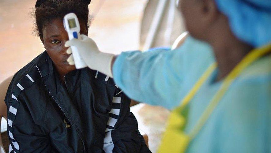 Une jeune fille suspectée d'être contaminée par le virus Ebola est contrôlée par  le personnel médical, le 16 août 2014 à Kenema, au Sierra Leone