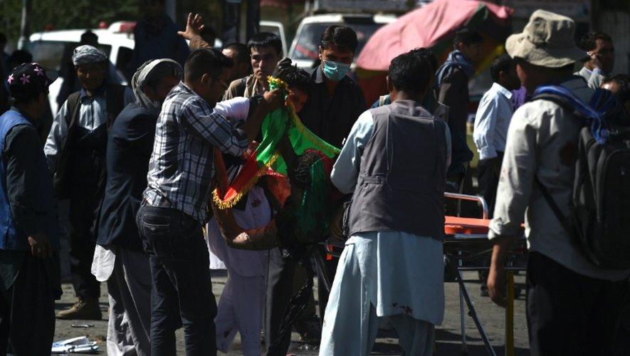 Des hommes transportent un corps après l'attentat qui a frappé une manifestation à Kaboul en Afghanistan, le 23 juillet 2016