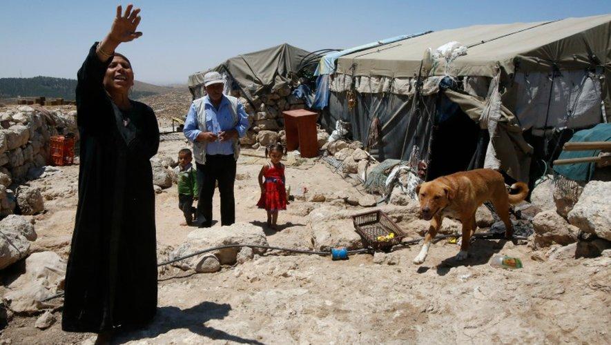 Shafiq al-Tal (c) entouré de sa famille est devant sa tente dans le village palestinien de Khirbet Zannouta, près de Hébron, le 30 mai 2016