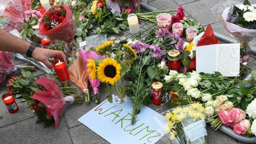 """Bougies, fleurs et note où est inscrit """"Pourquoi"""" rendent hommage aux neuf victimes du forcené, à l'entrée du centre commercial de Munich le 23 juillet 2016"""