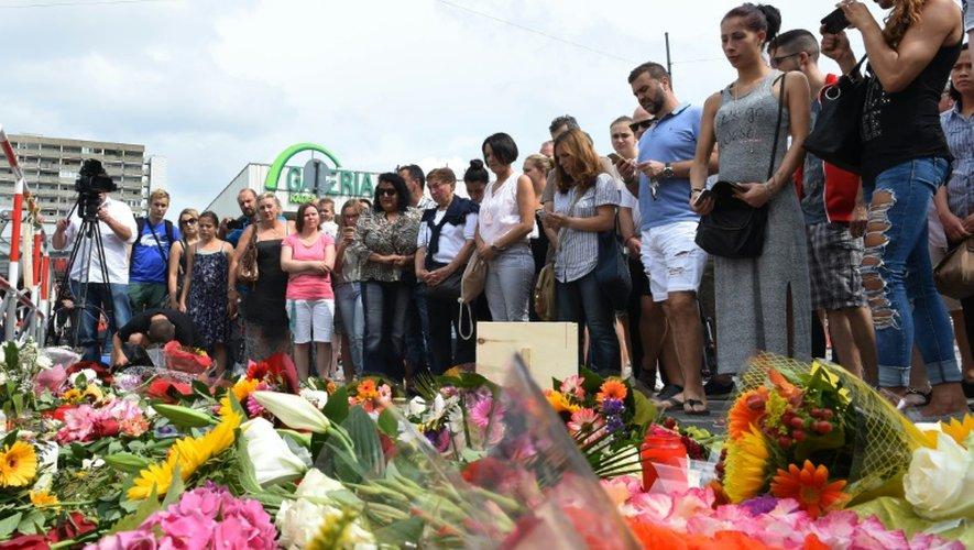 La foule rend hommage aux personnes abattues par le jeune forcené, dans un centre commercial à Munich, le 23 juillet 2016
