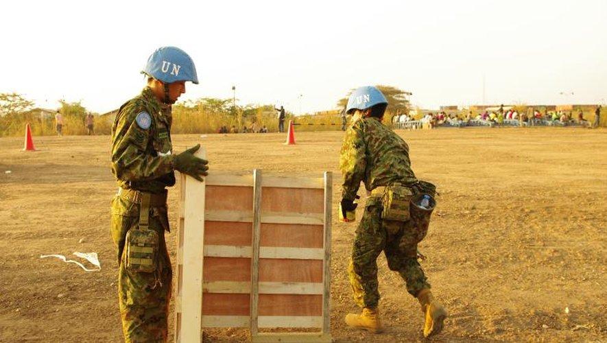 Photo fournie par la Mission de l'ONU au Soudan du Sud (Minuss) le 19 décembre 2013 de deux Casques bleus japonais en train de construire des latrines pour des réfugiés, le 17 décembre 2013 à Juba