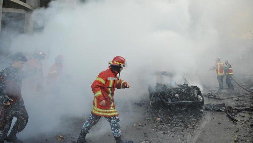 Des membres des forces de sécurité libanaises et des pompiers inspectent le site de l'attentat à la voiture piégée qui a frappé le centre de Beyrouth le 27 décembre 2013