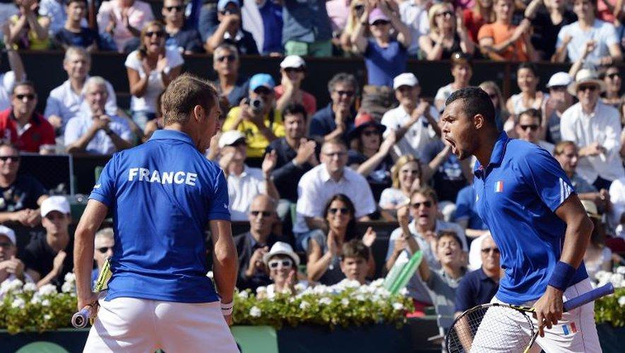 Richard Gasquet (g) et Jo-Wilfried Tsonga fêtent leur victoire en double contre la paire tchèque Berdych-Stepanek en demi-finale de Coupe Davis, le 13 septembre 2014 à Roland-Garros