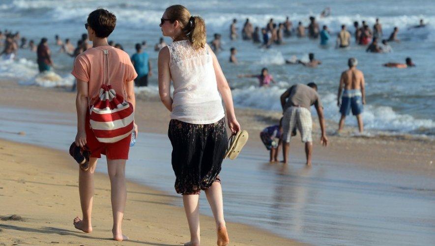 Des touristes se promènent sur la plage de Mount Lavinia, sud de Colombo, le 3 juillet 2016