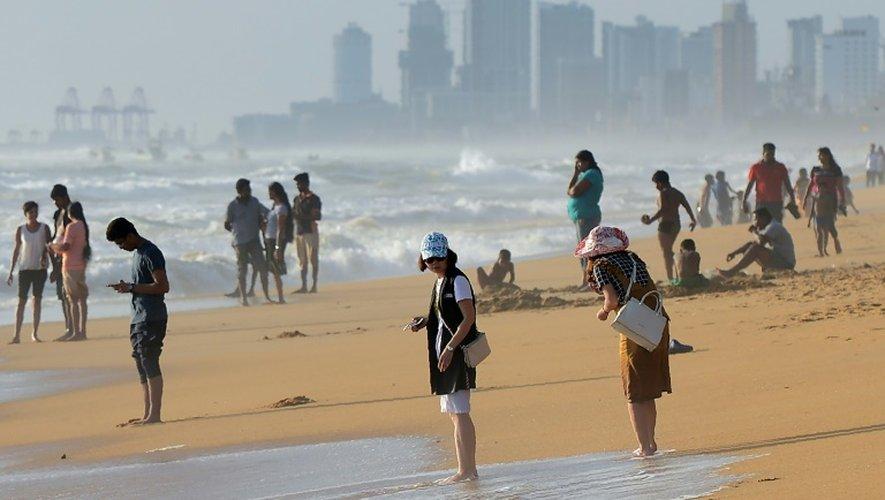 Des touristes se promènent le long de la plage de Mount Lavinia,  près de Colombo, le 3 juillet 2016