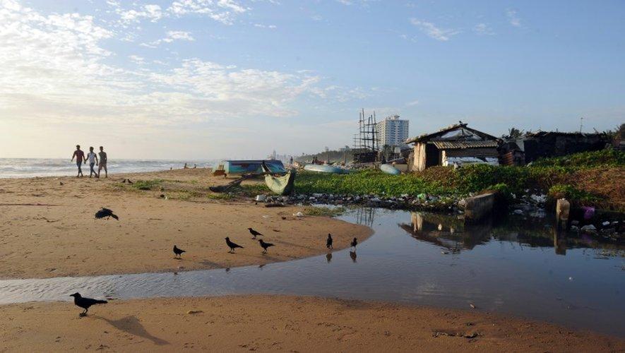 Des promeneurs sur la plage de Mont Lavinia (sud du Sri Lanka) passent près d'une évacuation d'eaux usées, le 3 juillet 2016
