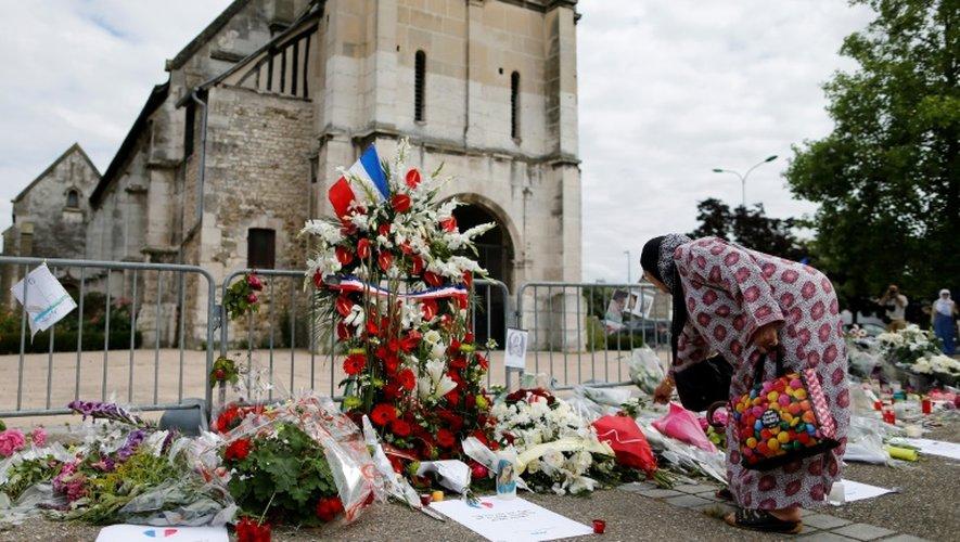Un femme dépose des fleurs devant l'église de Saint-Etienne-du-Rouvray, le 29 juillet 2016